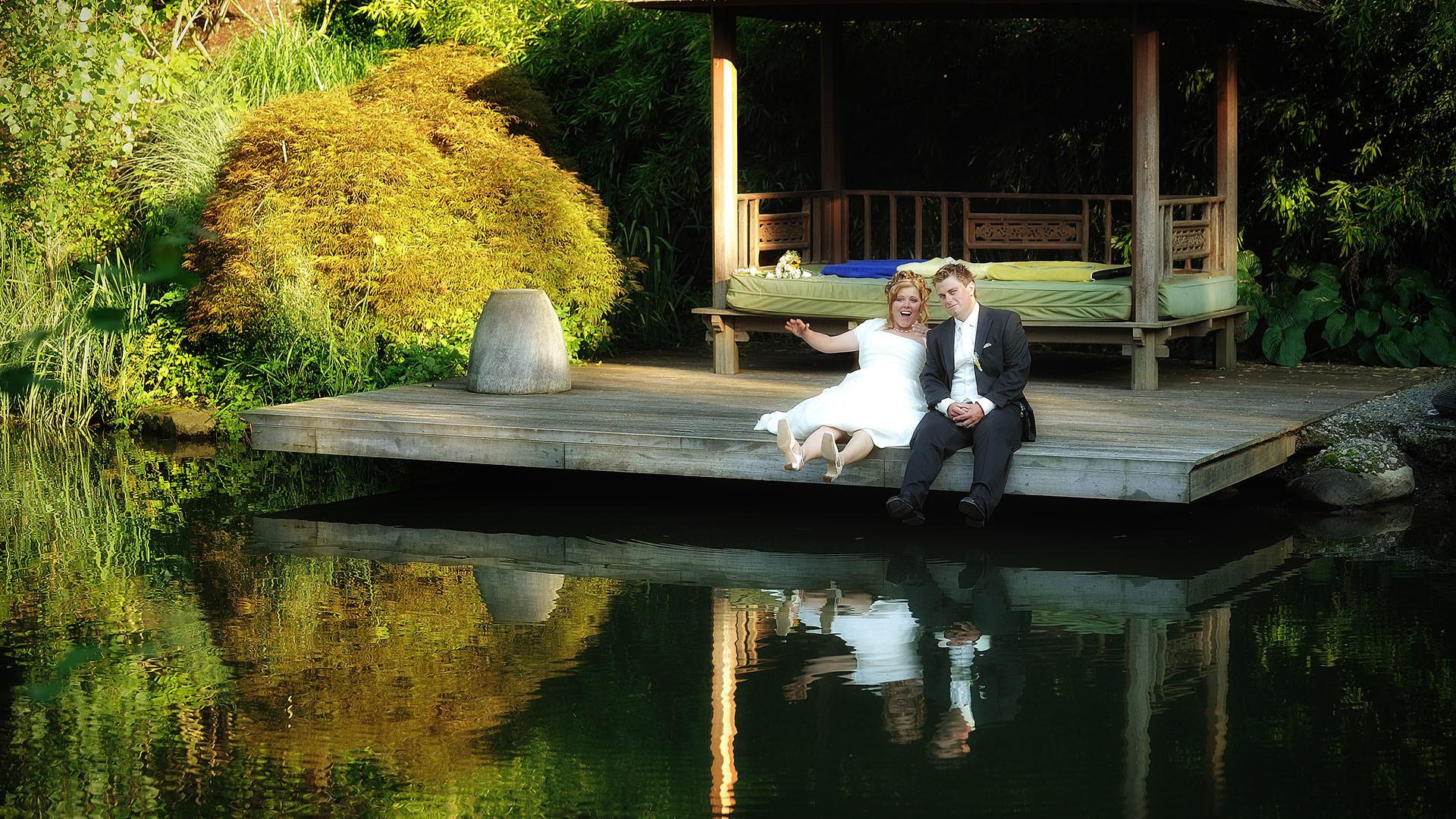 Hochzeitsfotograf mit Brautpaar am Teich